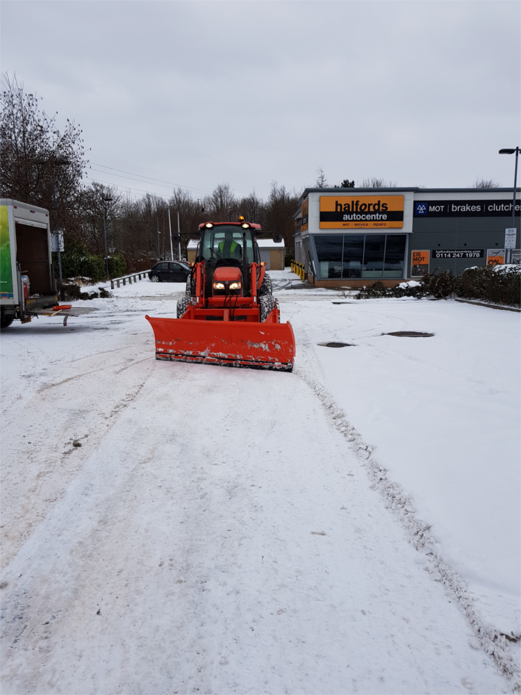 Snow plough removing snow from a Sheffield car park